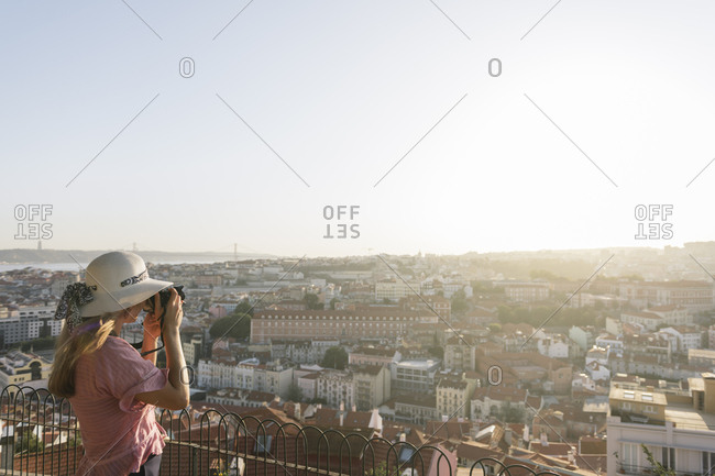 Woman taking a picture of the city panorama- Lisbon- Portugal