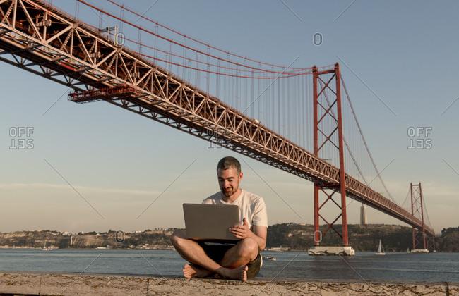 Man using laptop at 25th of April Bridge in Lisbon- Portugal