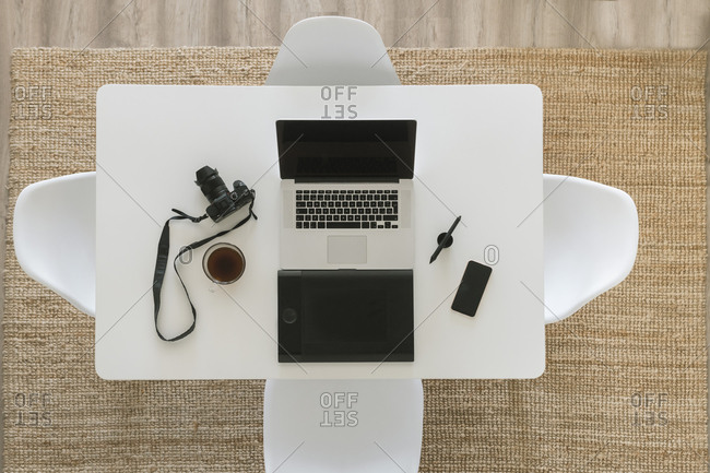 White table with camera- laptop- smartphone- cup of coffee and  graphics tablet- top view