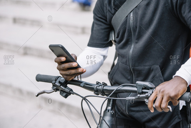 Close-up of man with bicycle using smartphone