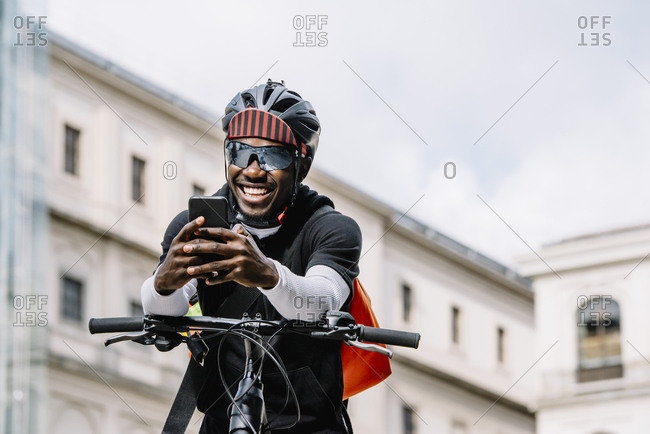 Happy stylish young man with bicycle- smartphone and messenger bag in the city