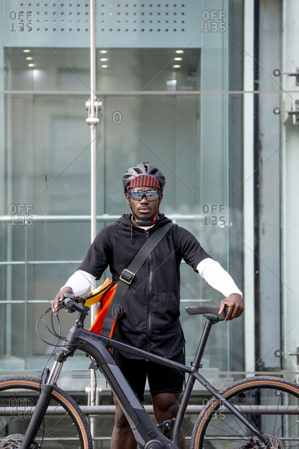 Portrait of stylish young man with bicycle and messenger bag in the city