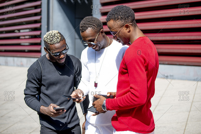 Three cool young men using cell phones in the city