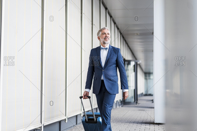Mature businessman in a passageway with rolling suitcase on the go