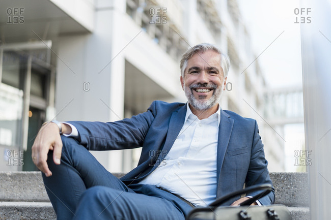 Portrait of smiling mature businessman sitting on stairs in the city