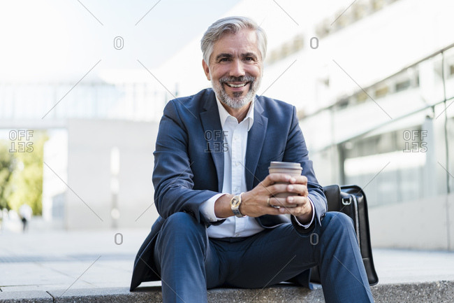 Portrait of smiling mature businessman sitting on stairs in the city holding takeaway coffee