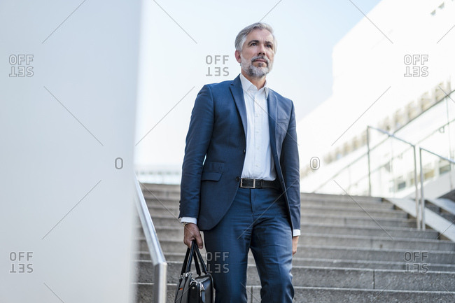 Mature businessman holding bag walking down stairs in the city
