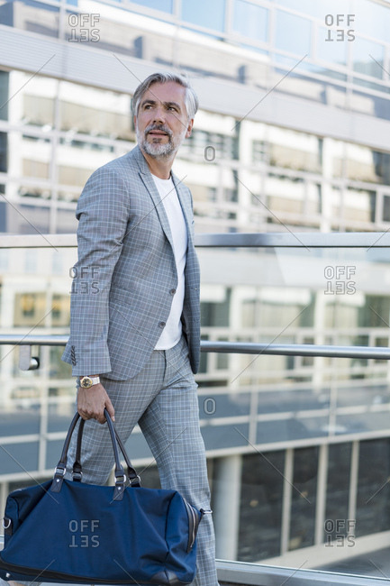 Fashionable mature businessman with travelling bag on the go