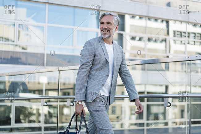 Smiling fashionable mature businessman with bag on the go