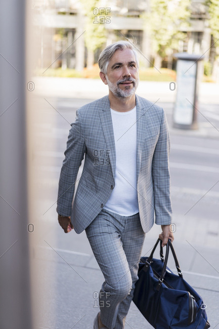 Fashionable mature businessman with travelling bag on the go in the city