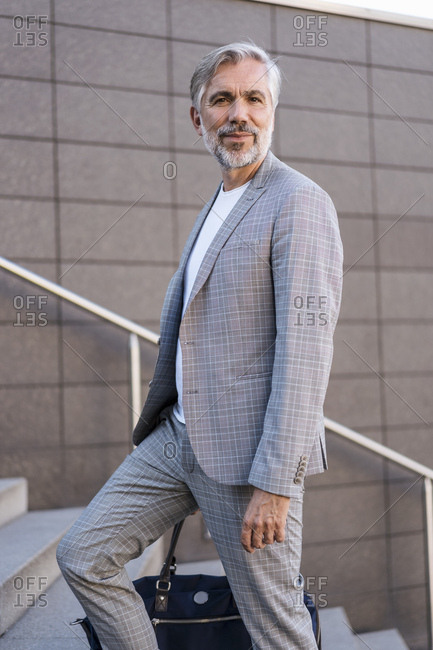 Portrait of fashionable mature businessman with bag on stairs