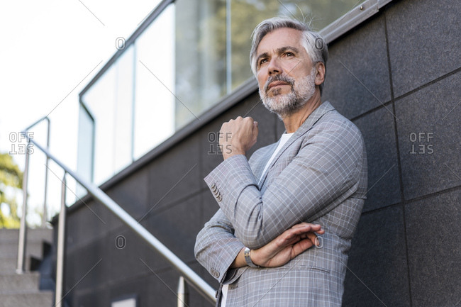 Fashionable mature businessman standing on stairs