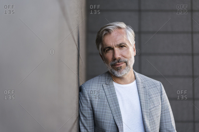 Portrait of fashionable mature businessman leaning at a wall