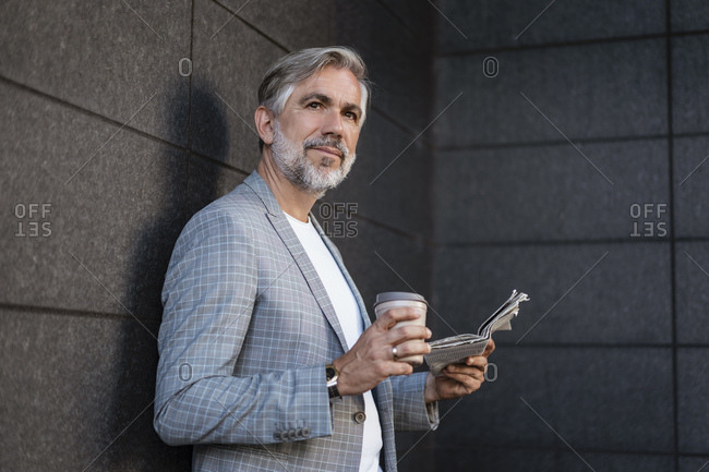 Fashionable mature businessman leaning at a wall with newspaper and takeaway coffee