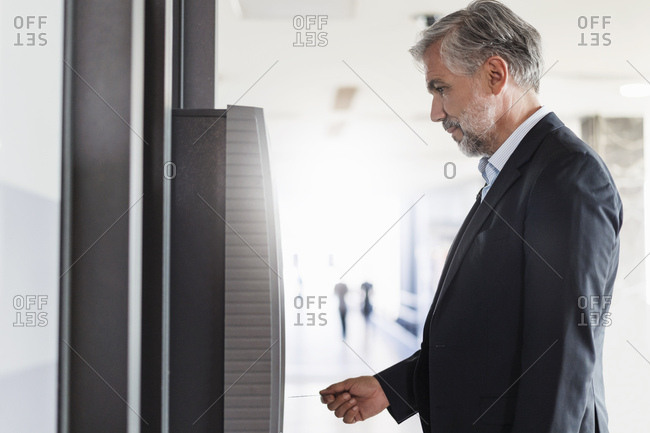 Businessman withdrawing money at an ATM