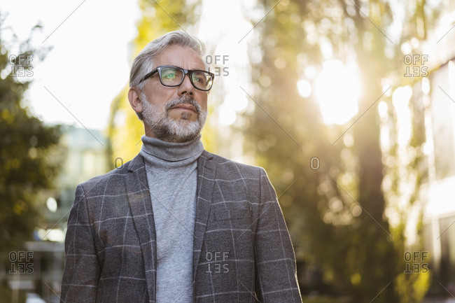 Portrait of fashionable mature businessman with glasses outdoors