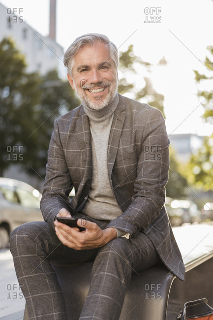 Portrait of smiling fashionable mature businessman in the city