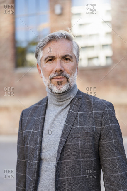 Portrait of fashionable mature businessman at a brick building