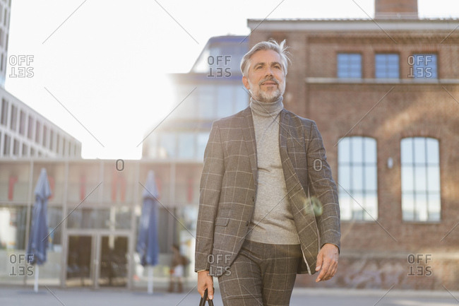 Fashionable mature businessman with bag on the go in the city