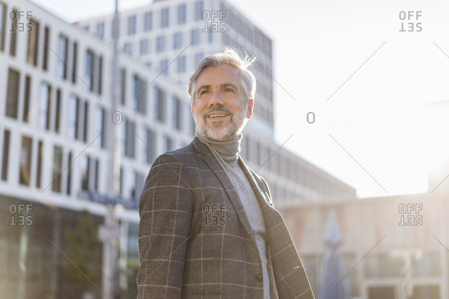 Portrait of fashionable mature businessman in the city looking around