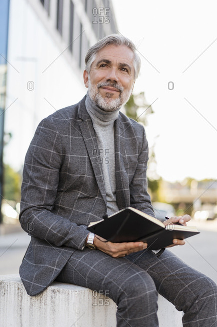 Fashionable mature businessman in the city sitting down with notebook