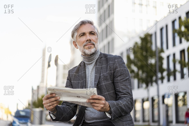 Fashionable mature businessman reading newspaper in the city