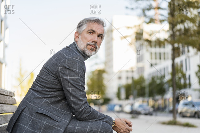 Portrait of fashionable mature businessman sitting on a bench in the city