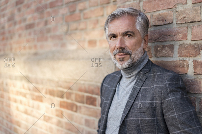 Portrait of fashionable mature businessman at a brick wall