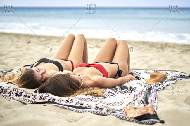Two young women lying on a towel a beach