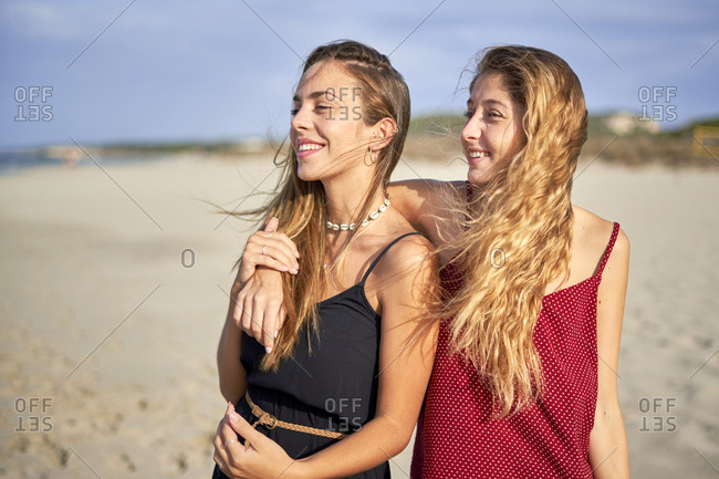 Two young women standing arm in arm on a beach