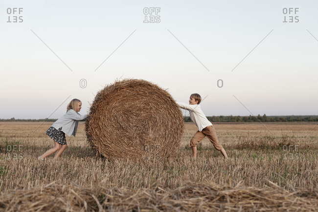 Two kids rolling a haystack on the field