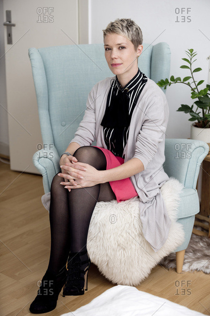 Portrait of fashionable woman with dyed short hair sitting on armchair at home