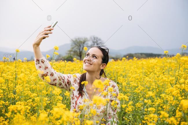 Portrait of happy woman taking selfie with smartphone in a rape field- Gyeongju- South Korea
