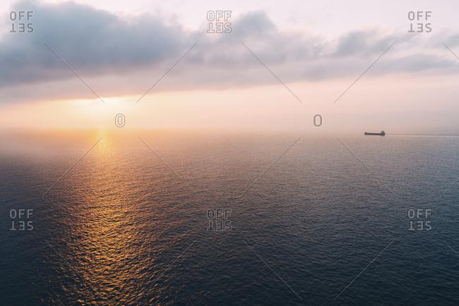 Cargo ship sailing towards sunset at horizon- Mallorca- Spain