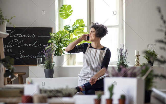 Smiling young woman on the phone in a small shop with plants
