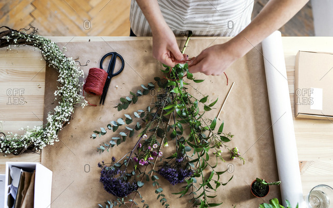 Close-up of woman arranging flowers in a small shop