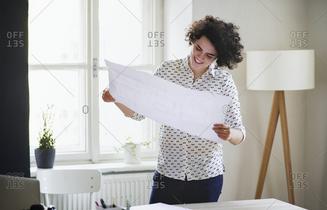 Smiling young woman studying a plan in office