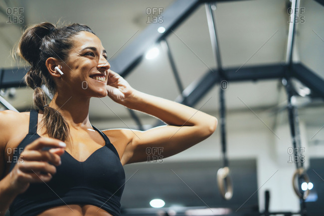 Smiling woman in good shape using earphones in a gym