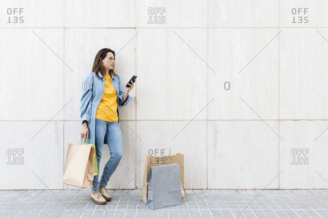 Young brunette woman using smartphone after shopping