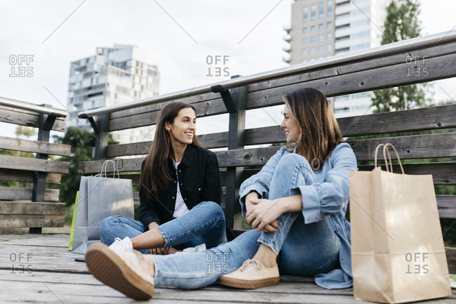 Two friends sitting on the floor after shopping- with the bags at their sides