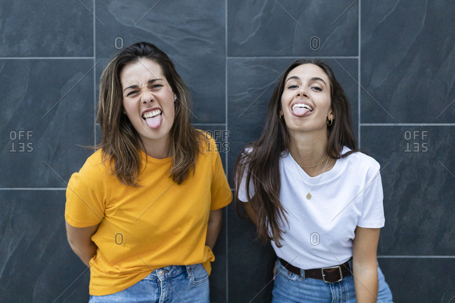 Two friends leaning on a wall and sticking out her tongues