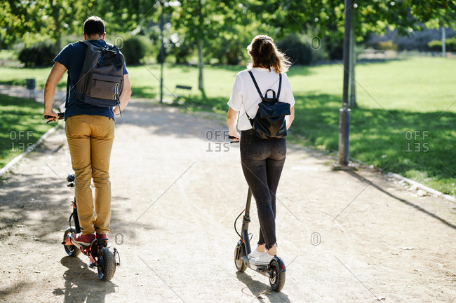 Back view of couple riding electric scooters in a city park