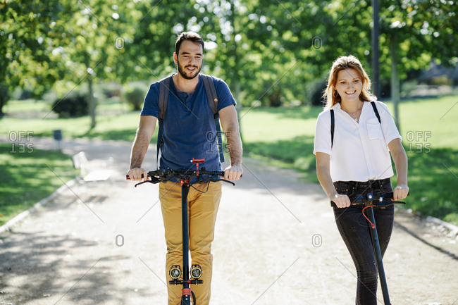 Portrait of content couple riding electric scooters in a city park