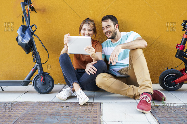 Portrait of smiling couple with electric scooters using digital tablet