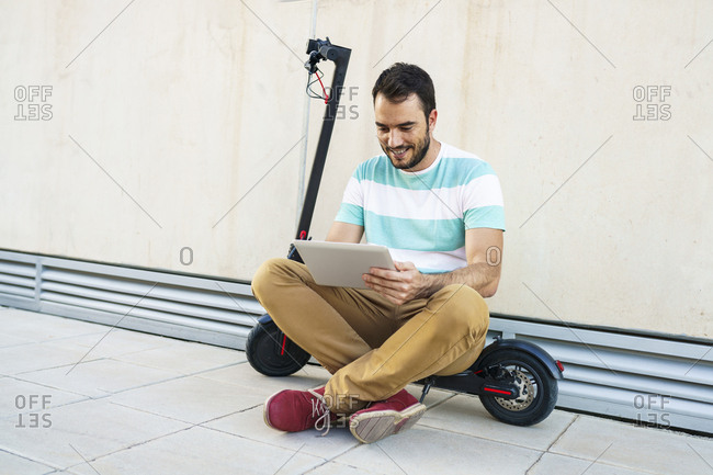 Portrait of man sitting on electric scooter using digital tablet