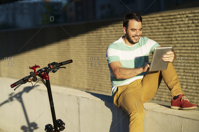 Portrait of smiling man with electric scooter using digital tablet