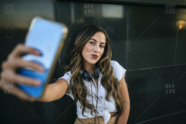 Young woman taking a selfie with her smartphone- pouting mouth
