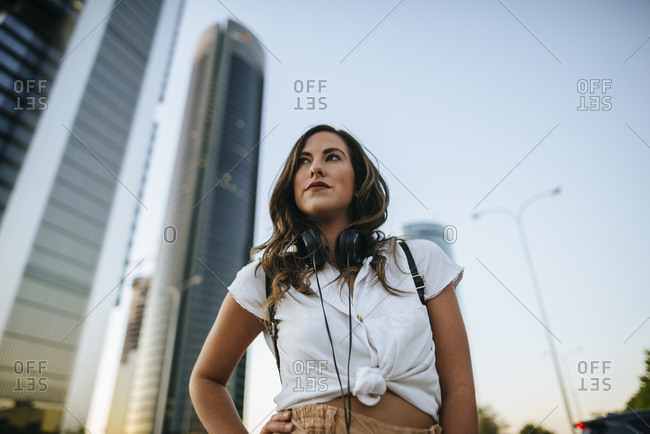 Young woman with headphones around neck- skyscrapers in the background