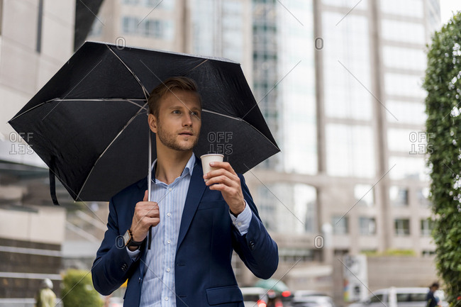 Young businessman with umbrella drinking a coffee during a rainy day in Bangkok