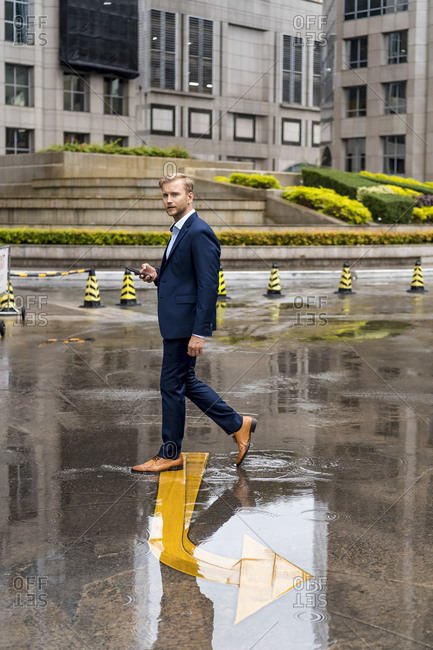 Young businessman with smartphone during a rainy day in Bangkok